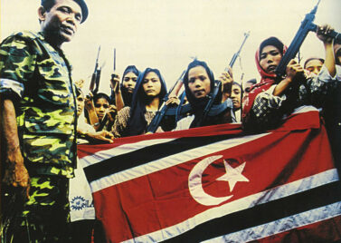 Women soldiers of the Free Aceh Movement (GAM) pose with commander Abdullah Syafei'i in 1999 (Source: Wikimedia Commons)