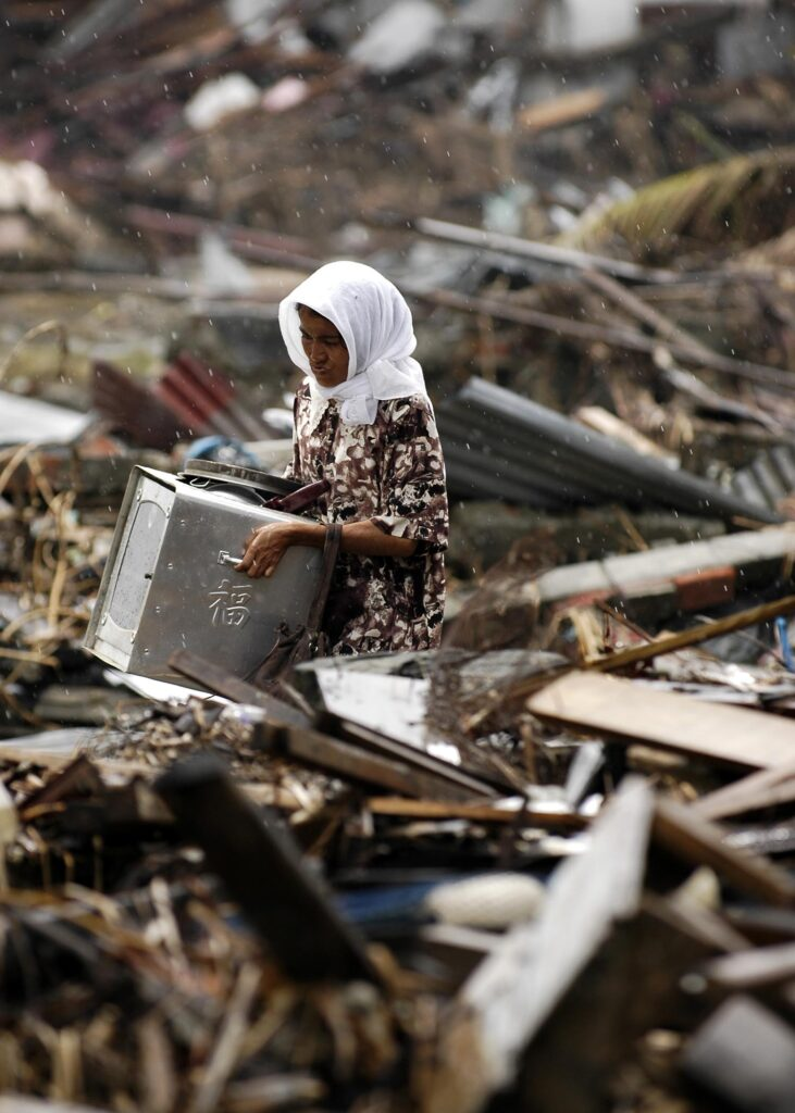 An Acehnese woman searches through the debris of where her house once stood (Source: Chuck Simmins)